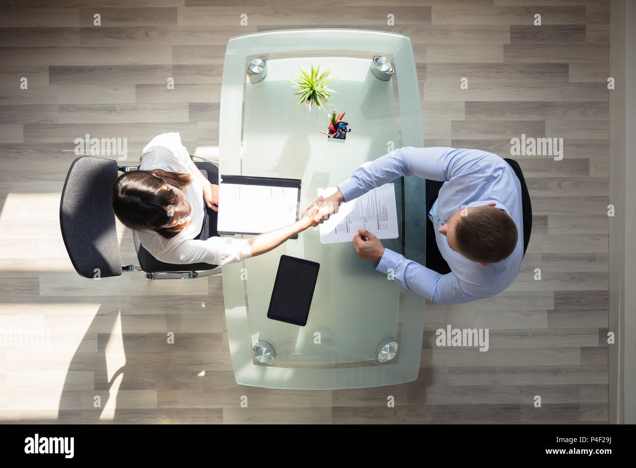 Elevated View Of Businessman Shaking Hand With Female Applicant At Workplace - Stock Image