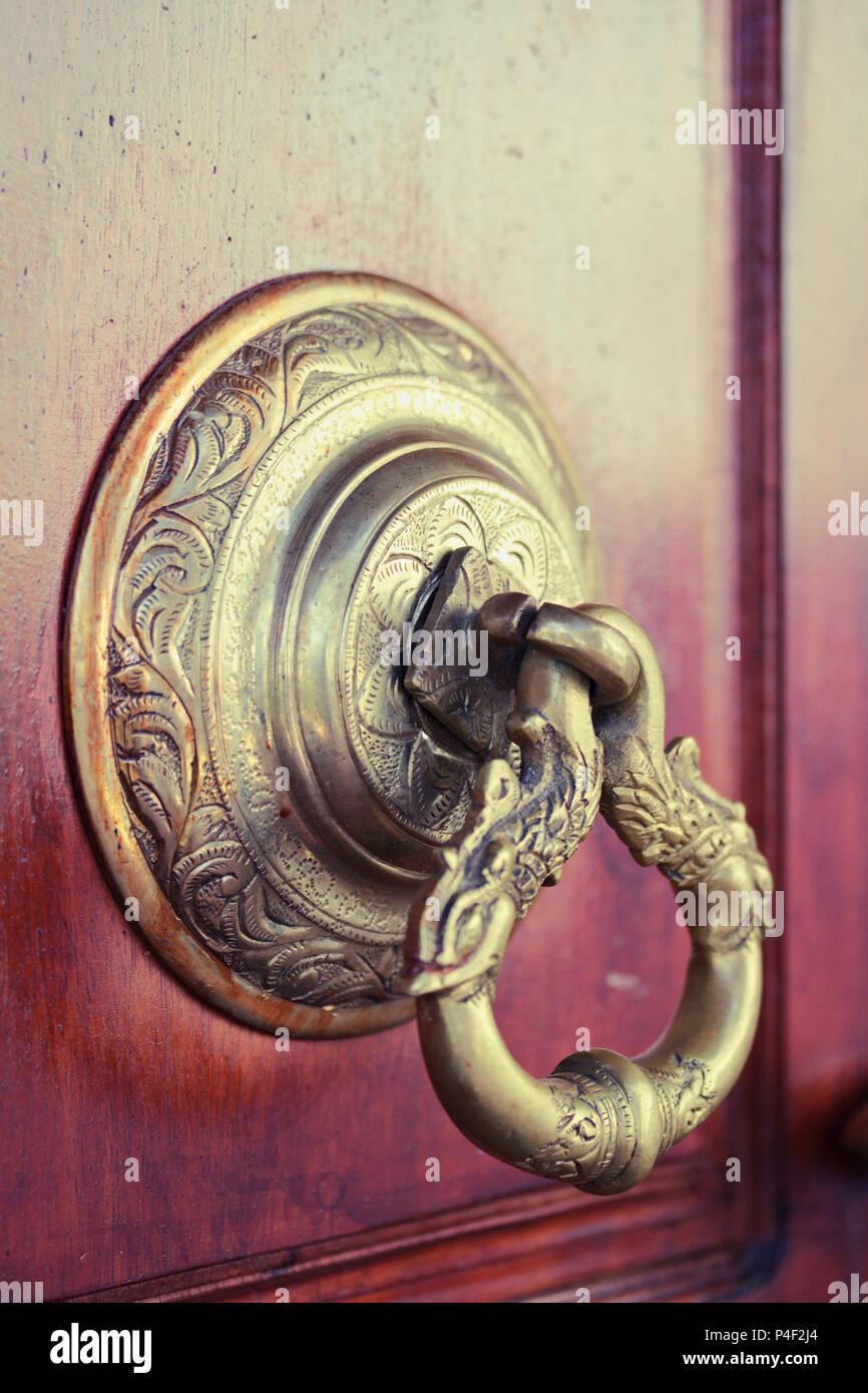 an antique indian doorknob at a temple door - Stock Image
