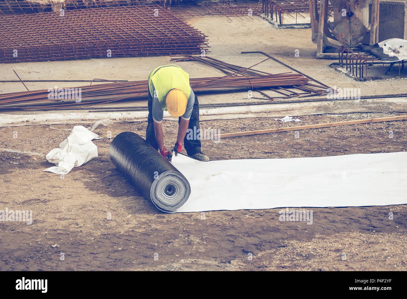 Insulation worker preparing bituminous waterproof membrane for waterproofing and protecting at construction site. Vintage style. - Stock Image