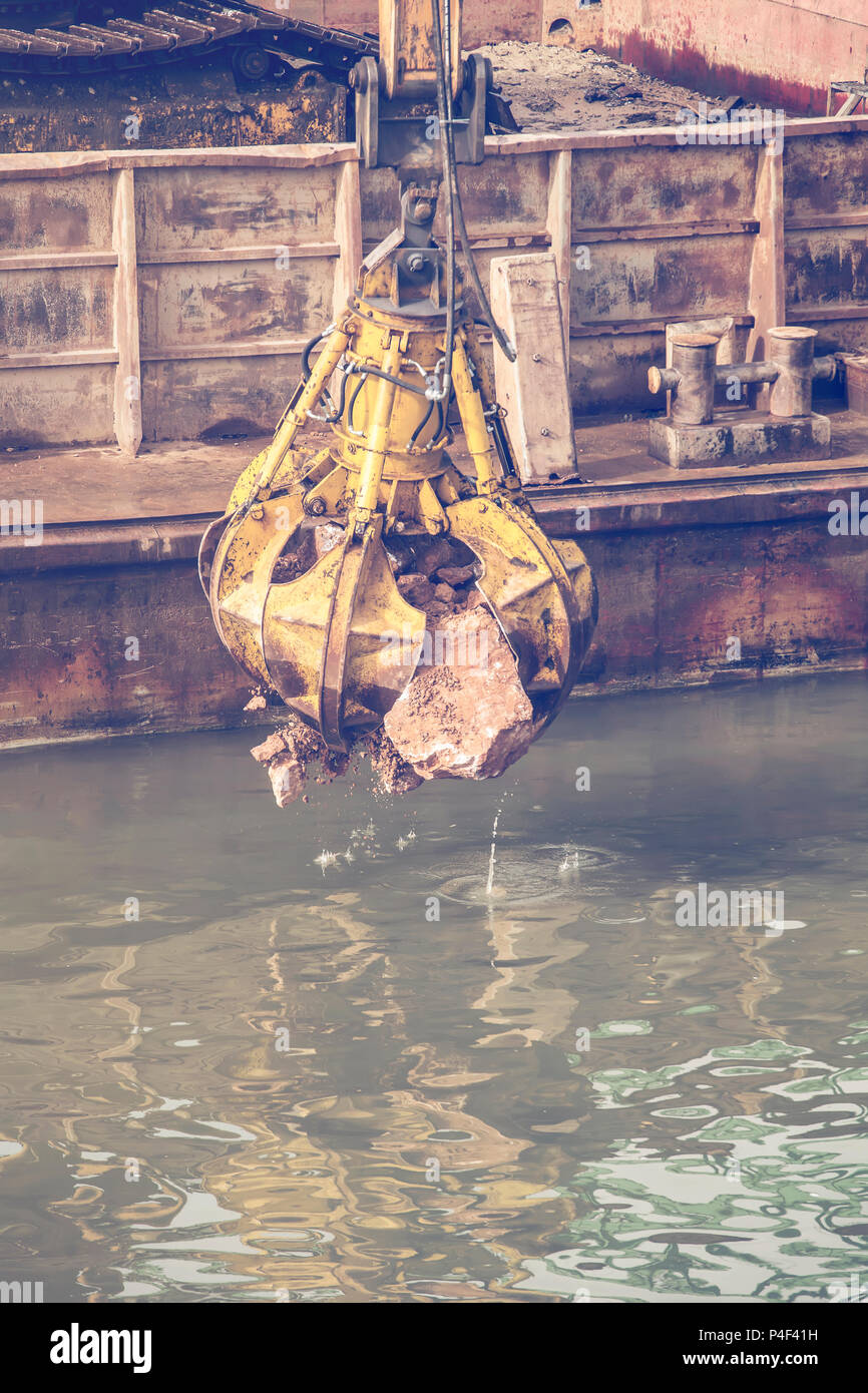 Excavator on barge with hydraulic rotator stone grab in action from river barge, working on river revetment construction site. Vintage style. - Stock Image