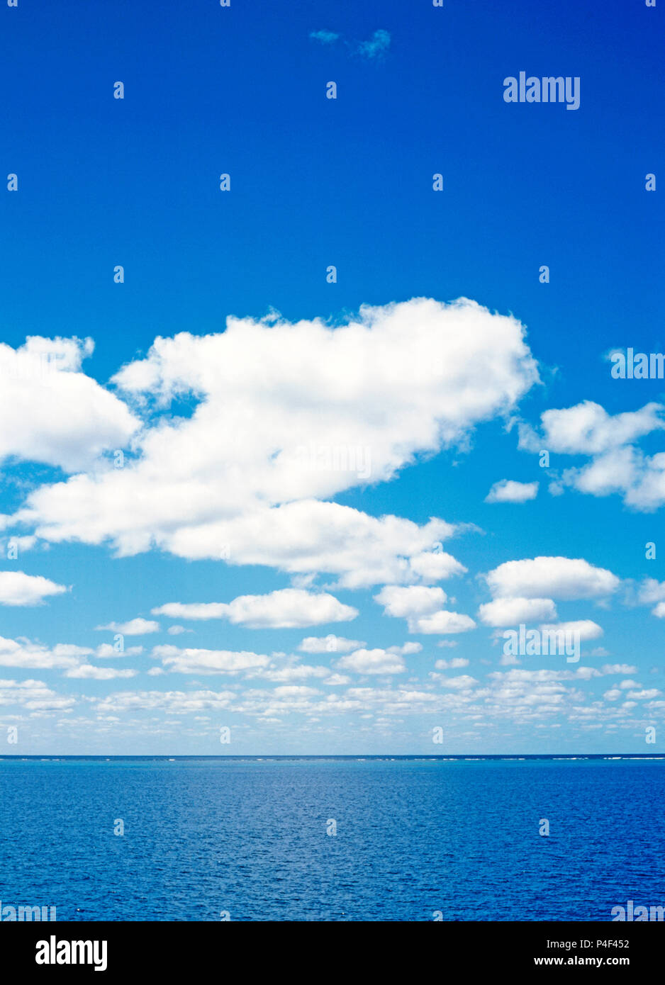 Blue sky with fluffy white clouds over Pacific Ocean horizon of Great Barrier Reef, Queensland, Australia. - Stock Image