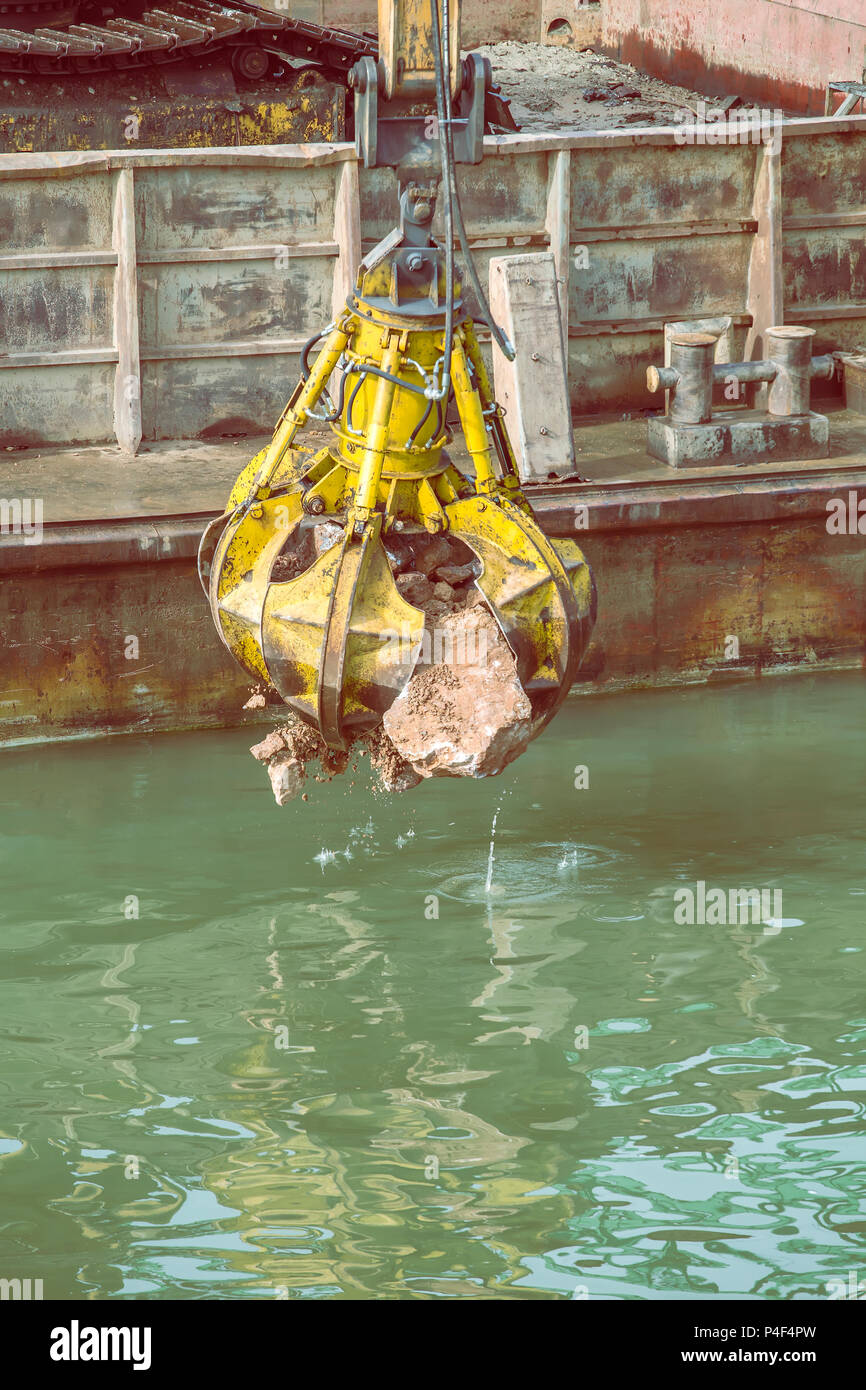 Excavator on barge with hydraulic rotator stone grab in action from river barge, working on river revetment construction site. Vintage style - Stock Image