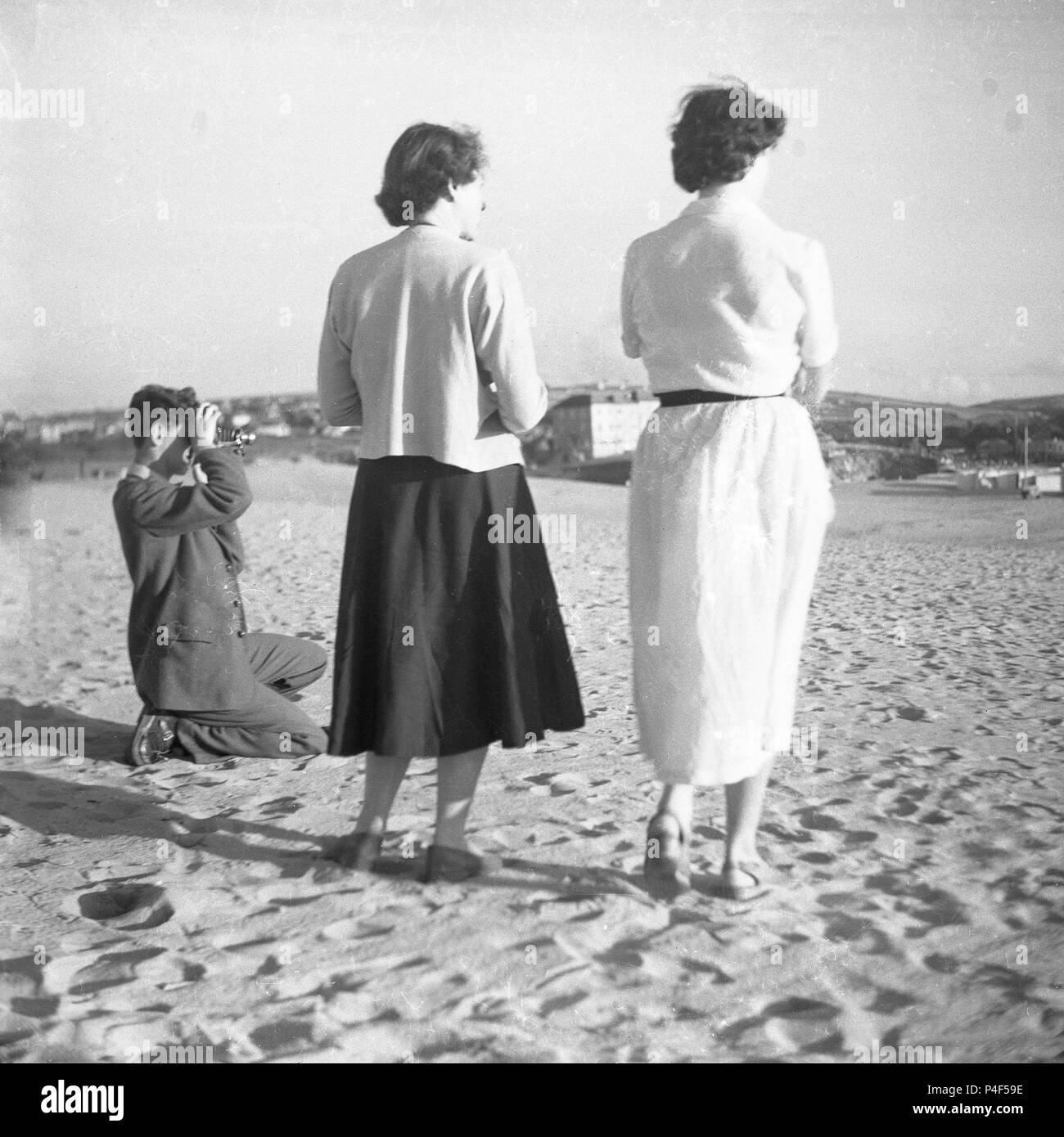 1950s, two ladies standing together on a sandy beach, while a gentleman kneeling down takes a photograph with his film camera (bellow), England, UK. - Stock Image