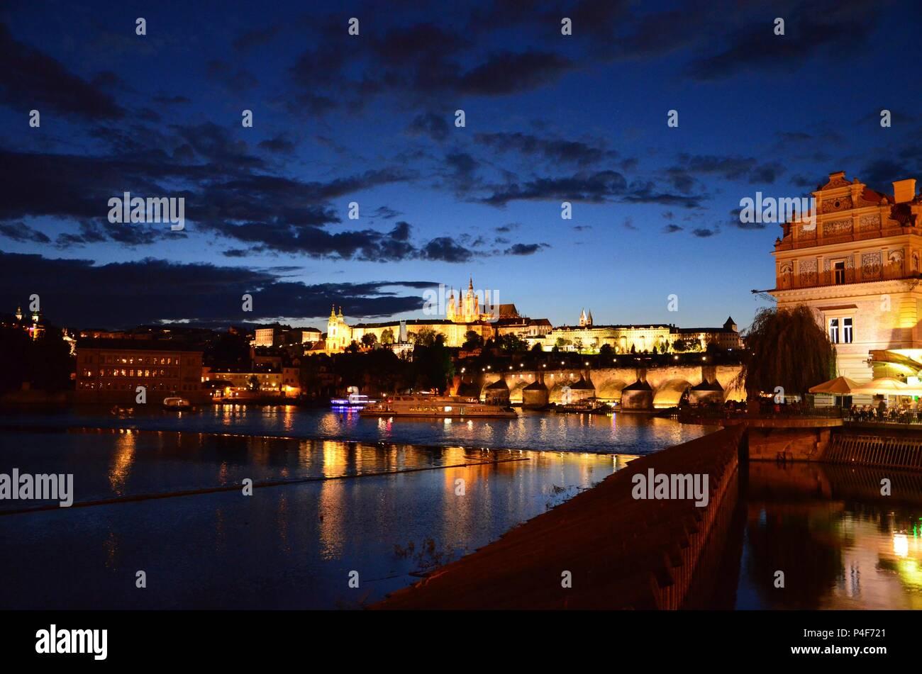 Illuminated Prague city along the river Moldau at night with view towards Charles Bridge and Castle - Stock Image