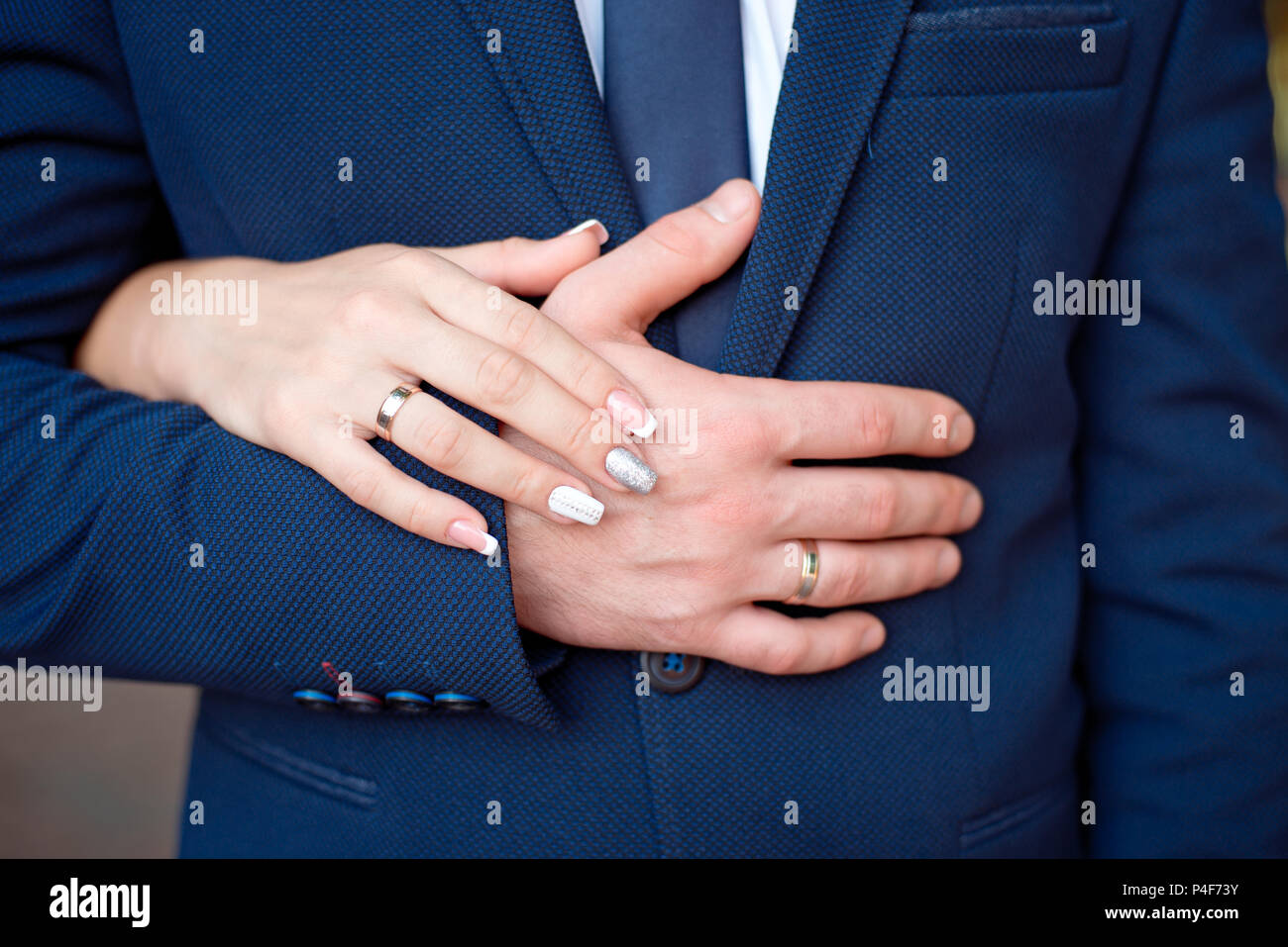 Close-up Bride and groom\'s hands with wedding rings. Groom putting ...
