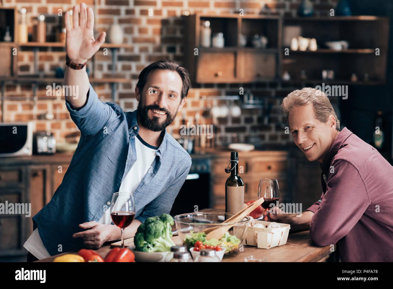 cheerful middle aged men drinking wine and waving hand while cooking together in kitchen - Stock Image