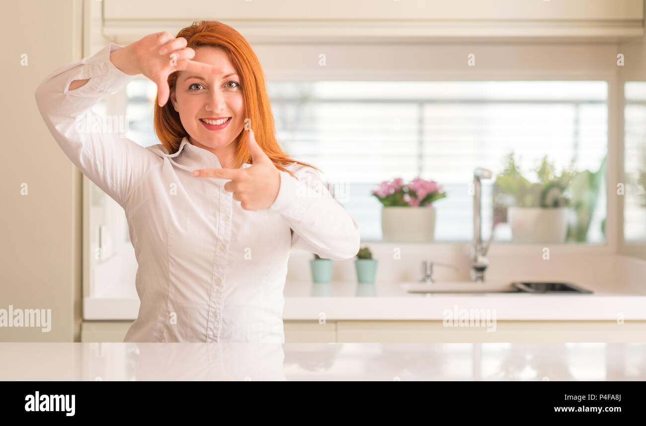 Redhead woman at kitchen smiling making frame with hands and fingers ...
