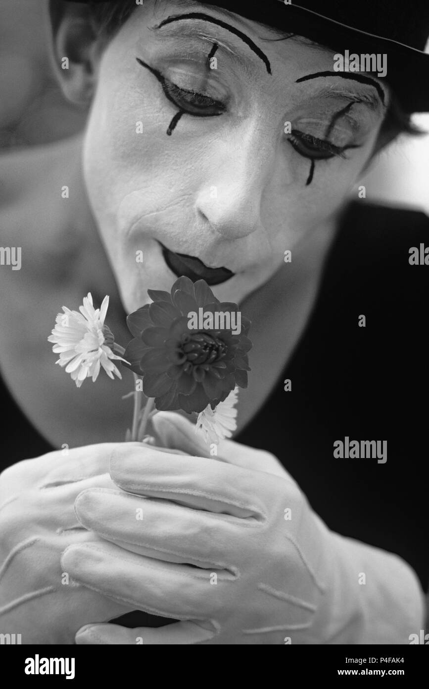 Mime performing at Seattle Center smelling flowers with white face and gloves Seattle Washington State USA - Stock Image