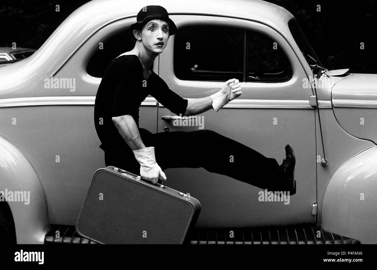 Mime running beside classic hot Rod Car - Stock Image
