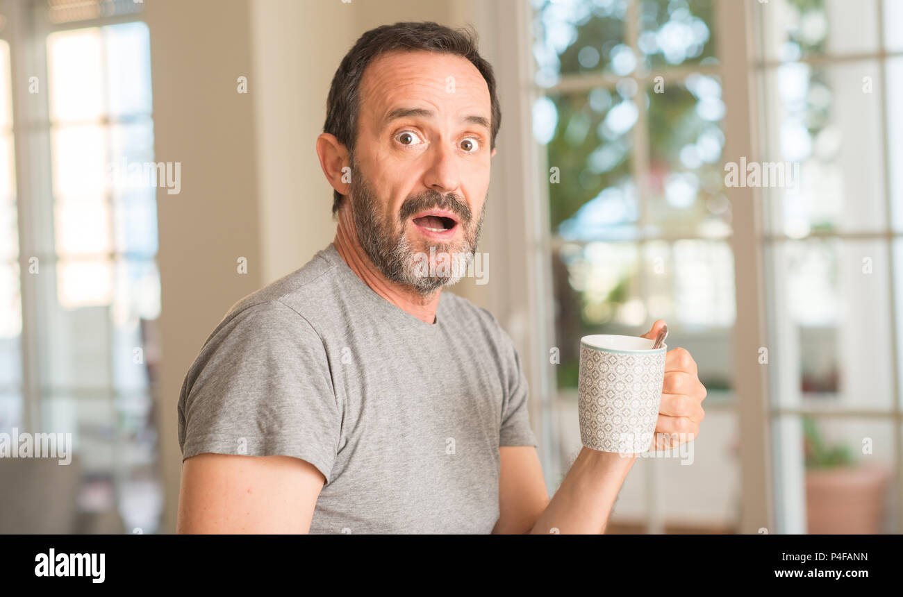 Middle age man drinking coffee in a cup scared in shock with