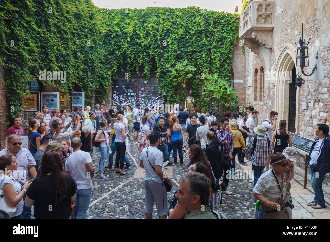 Verona, Italy – May 26, 2017: Crowed patio full of tourists visiting the statue under the famous balcony of Juliet's house Stock Photo