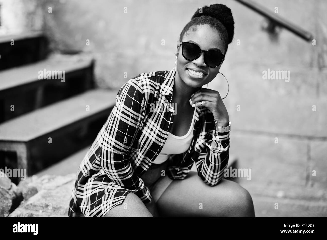 Hip hop african american girl on sunglasses and jeans shorts. Casual street fashion portrait of black woman. - Stock Image