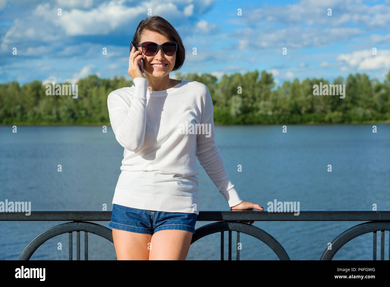 Adult beautiful smiling woman talking on the phone. Background river, sky with clouds, photo taken in summer. - Stock Image