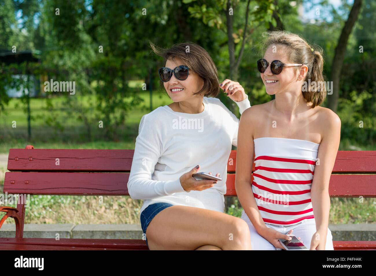 Mother and daughter teenager looking to the side, sitting on a bench in the park. Communication between parent and child. Copy space Stock Photo