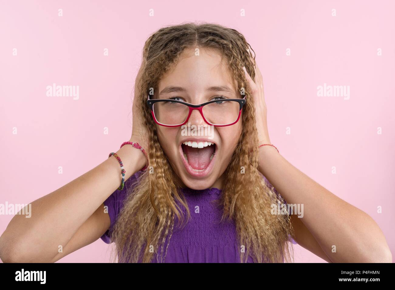 Delight, happiness, joy, victory, success and luck. Teen girl on a pink background. Facial expressions and people emotions concept - Stock Image