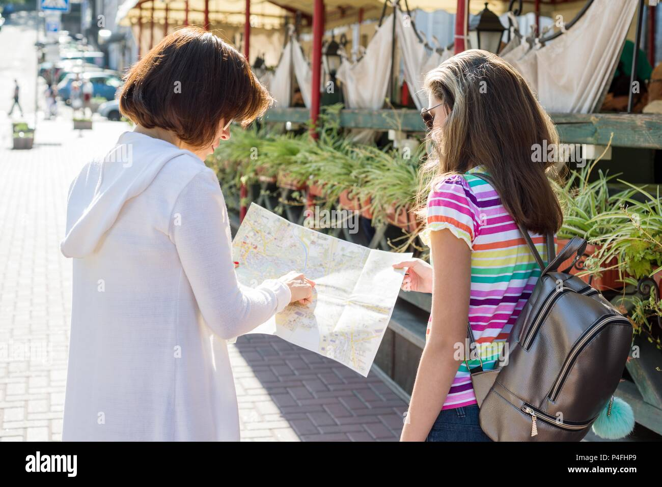 Back view of mom and daughter teen tourist looking at the map on the street of european city, travel to Europe - Stock Image
