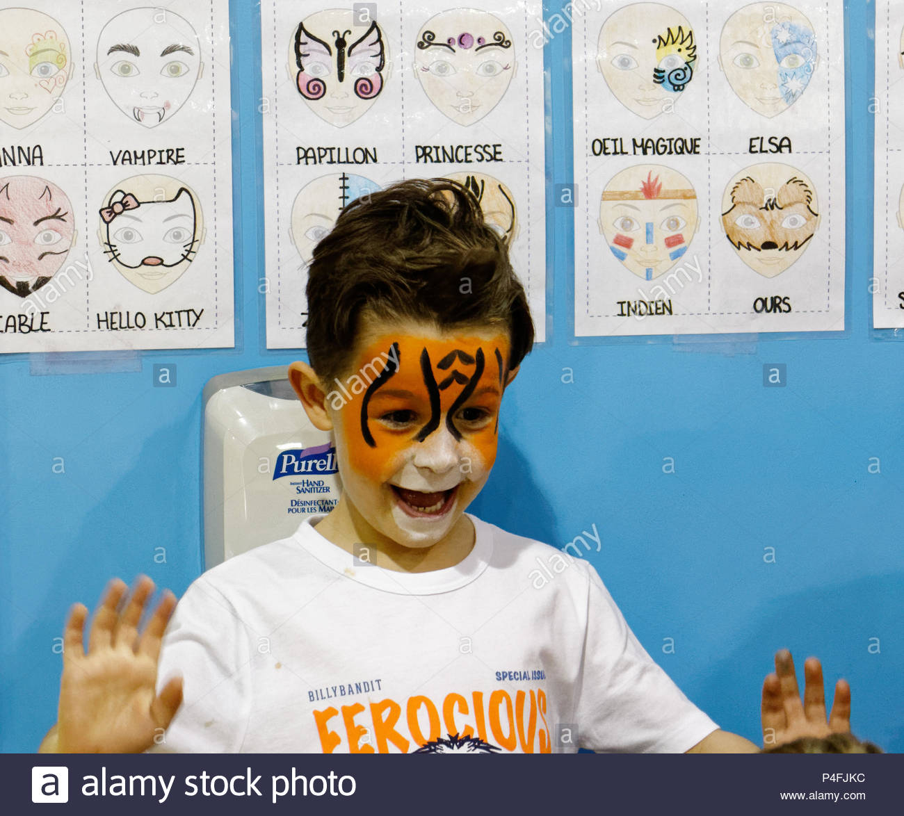 A five year old boy looks delighted with his new tiger face paint - Stock Image