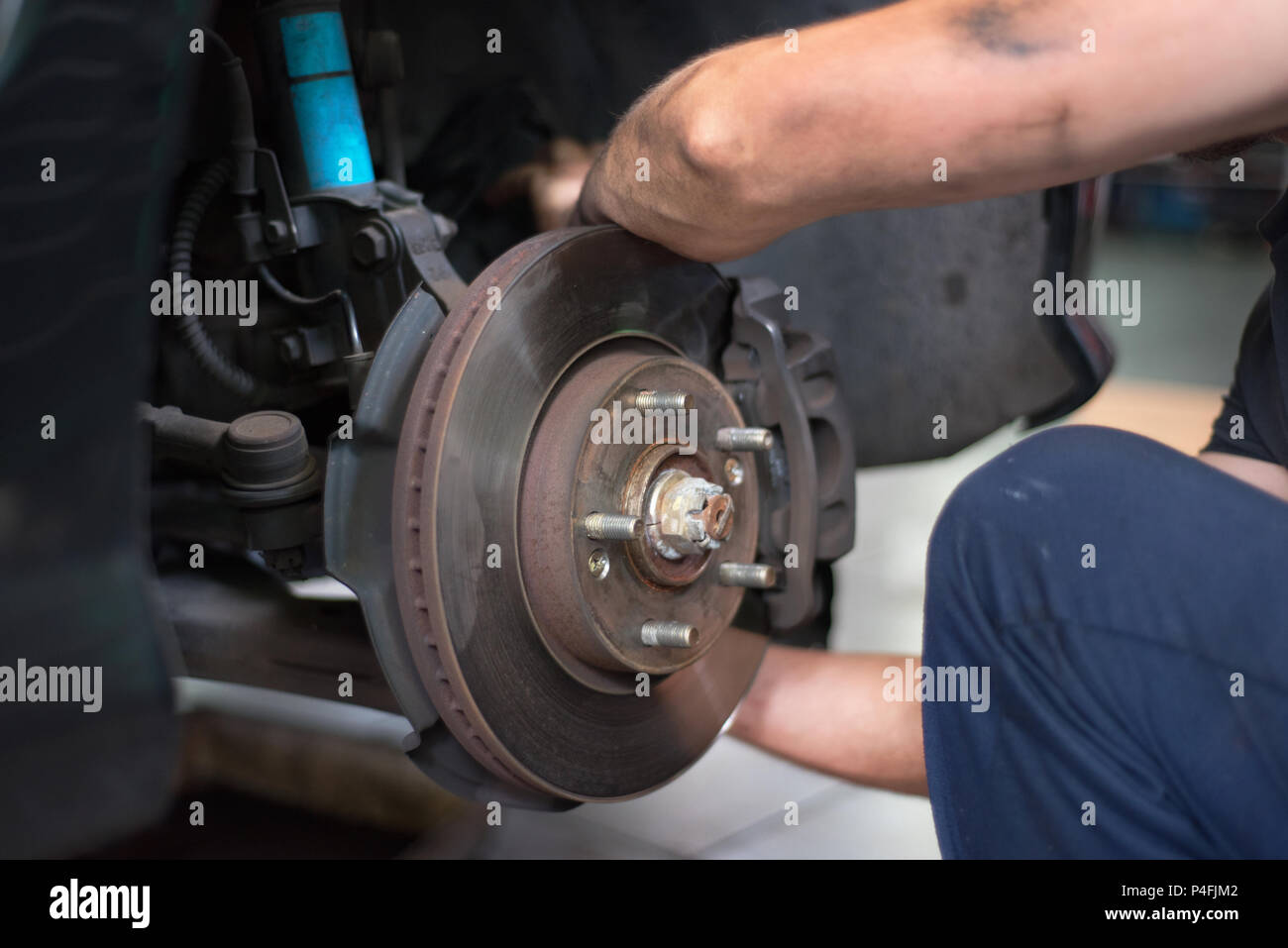 Close up of car mechanic repairing brake pads - Stock Image