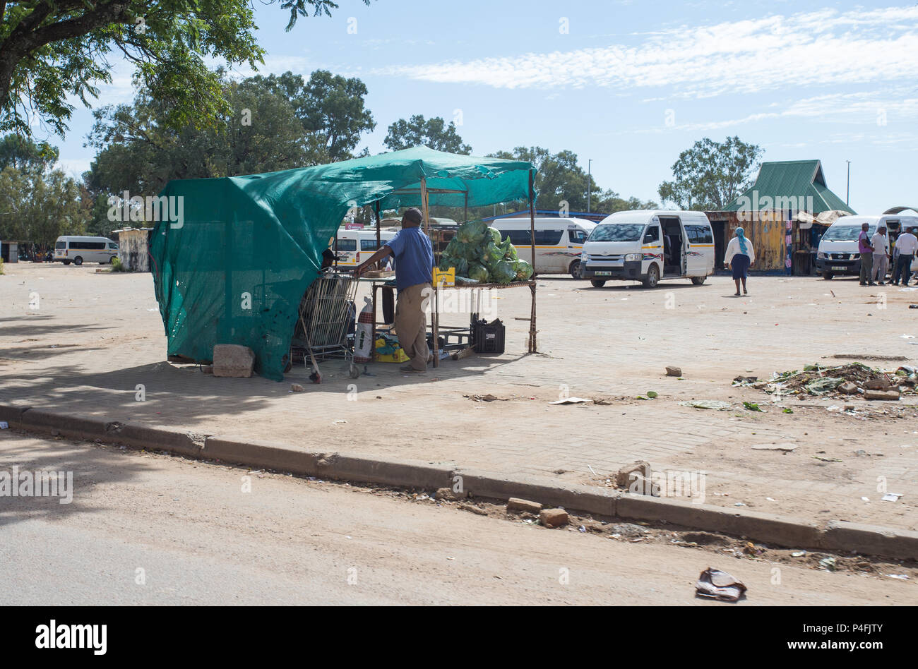 Rural African taxi rank with parked taxis and fruit and vegetable stall with vendor in Mahikeng, South Africa - Stock Image