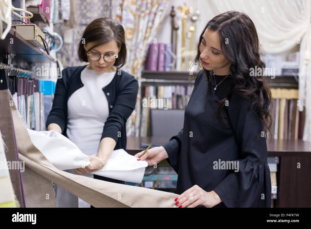 Woman Seller   Textile Designer Advises Woman Buyer. Selection Of Interior  Fabrics For Curtains, Bedspreads, Pillows. Decorating Shop