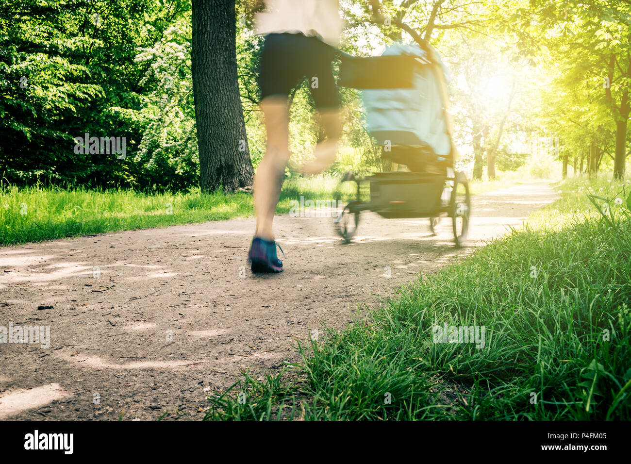 Running woman with baby stroller enjoying summer in park. Jogging or power walking supermom, active family with baby jogger, motion blur. - Stock Image