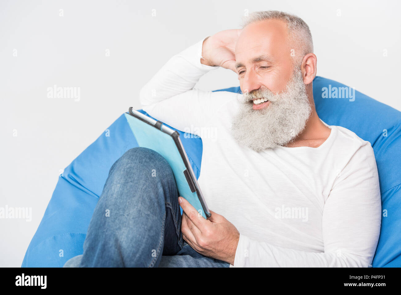 smiling senior bearded man using digital tablet while sitting in bean bag chair, isolated on white - Stock Image