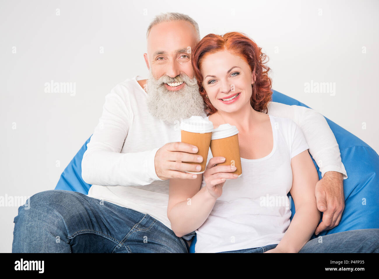 smiling mature couple drinking coffee from disposable cups while sitting in bean bag chair, isolated on white - Stock Image