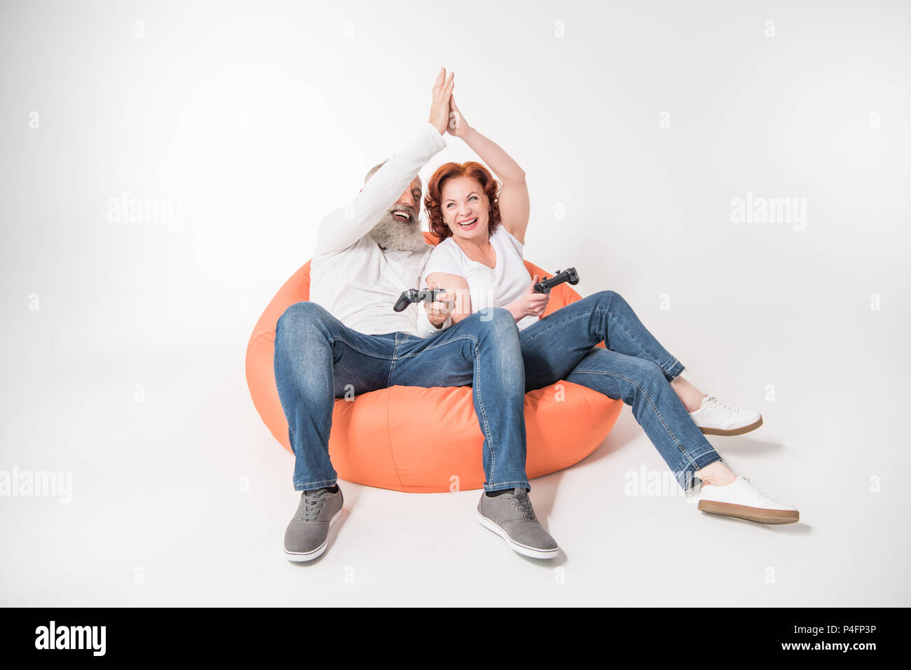 happy mature couple playing video game with joysticks and giving highfive while sitting in bean bag chair, isolated on white - Stock Image