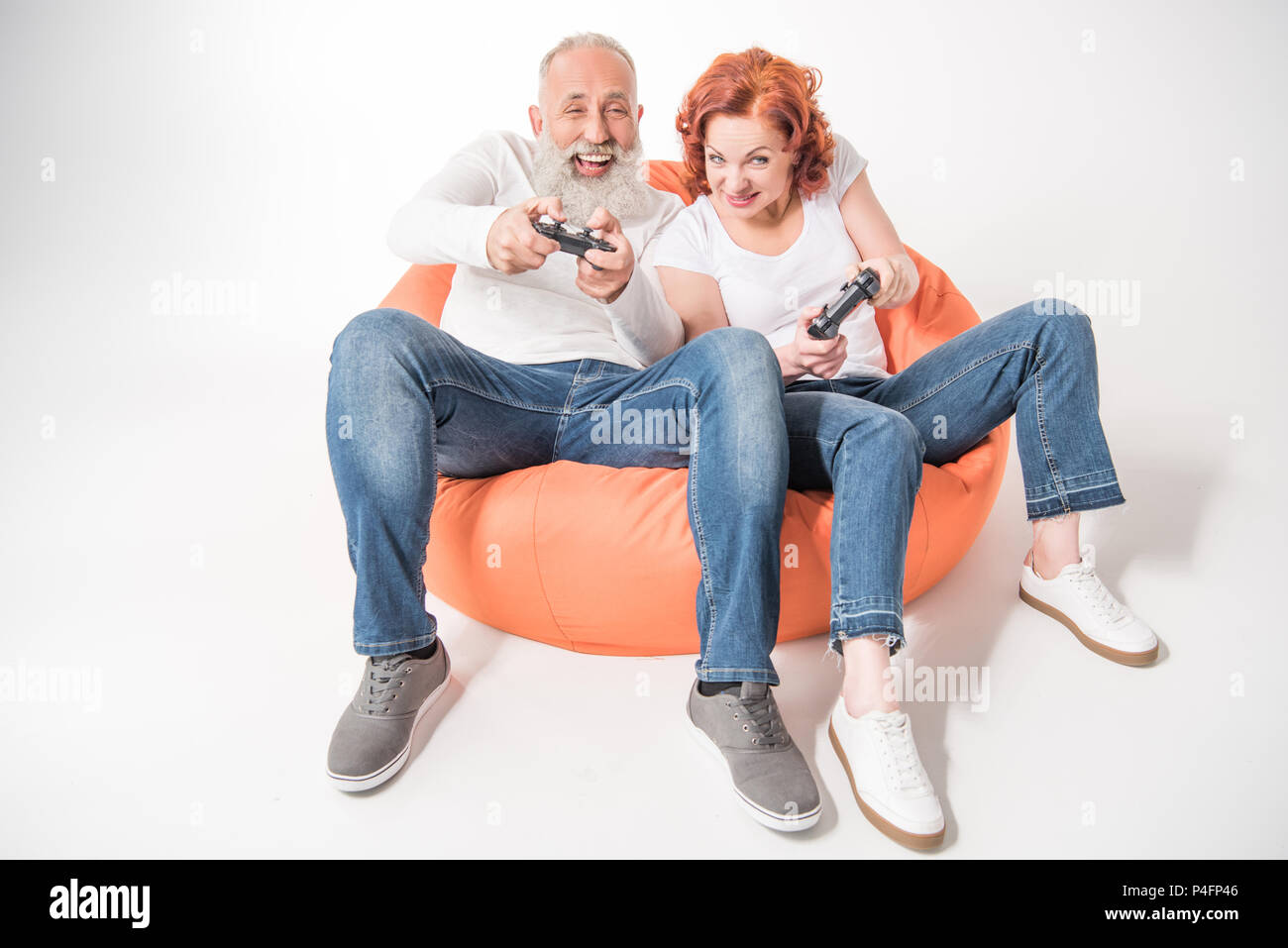 smiling mature couple playing video game with joysticks while sitting in bean bag chair, isolated on white - Stock Image