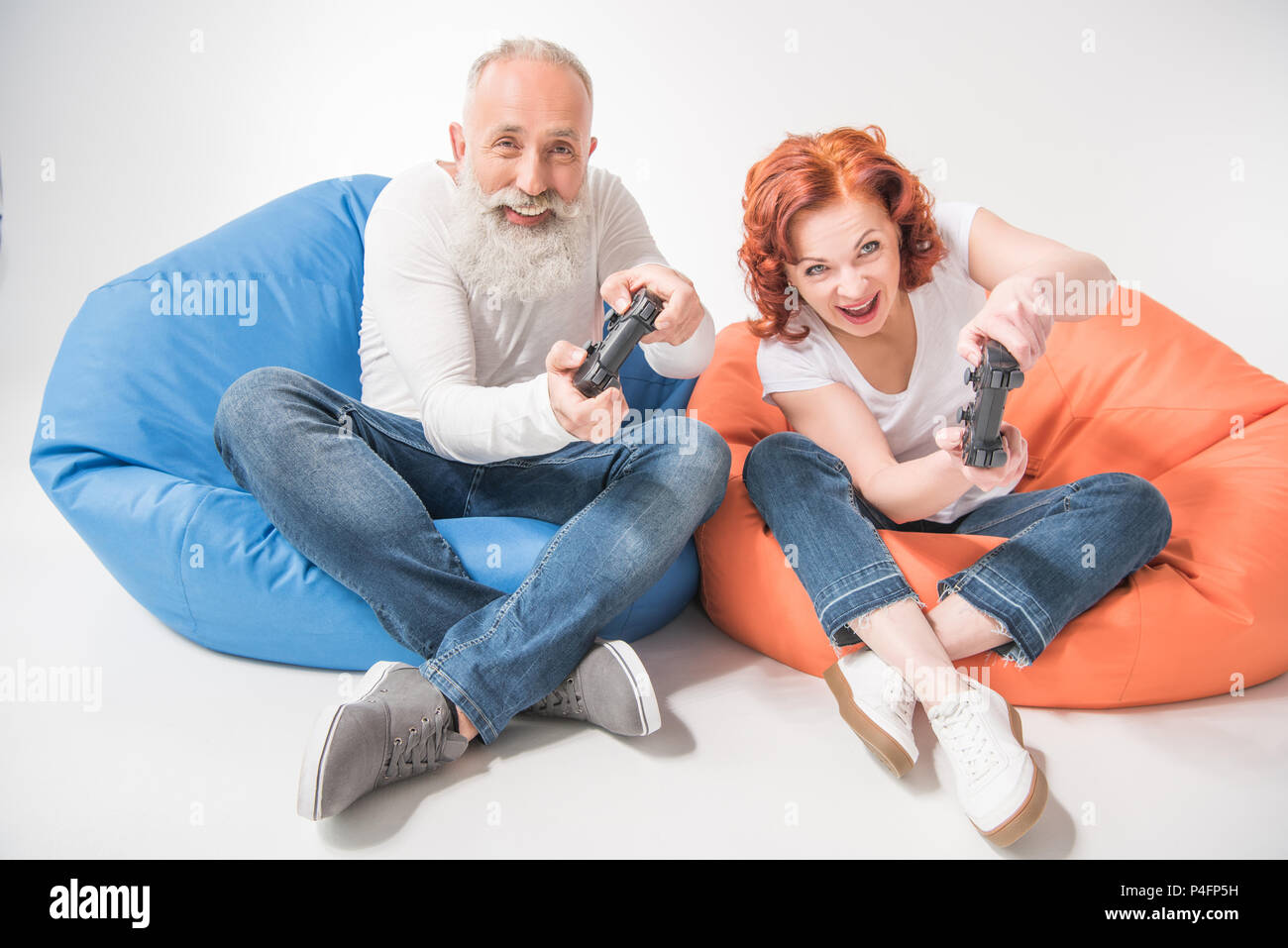 excited mature couple playing video game with joysticks while sitting in bean bag chairs, isolated on white - Stock Image