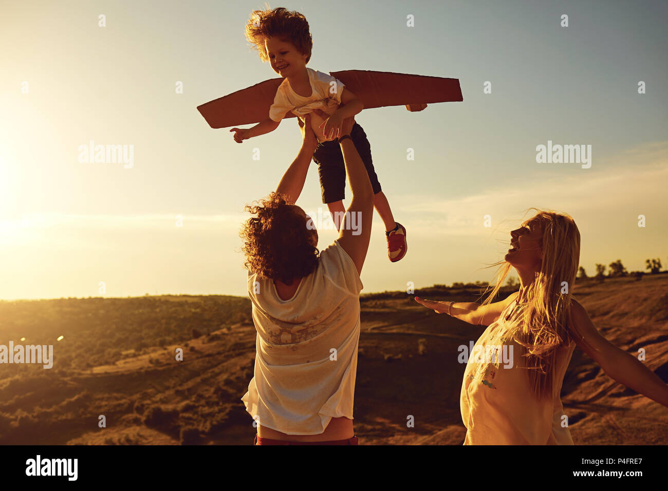 Family playing in nature at sunset - Stock Image