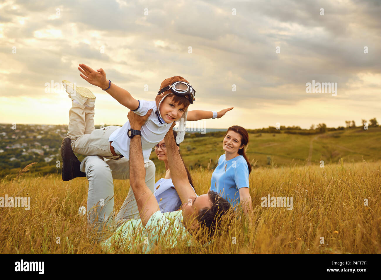 Happy family playing on grass in nature at sunset - Stock Image