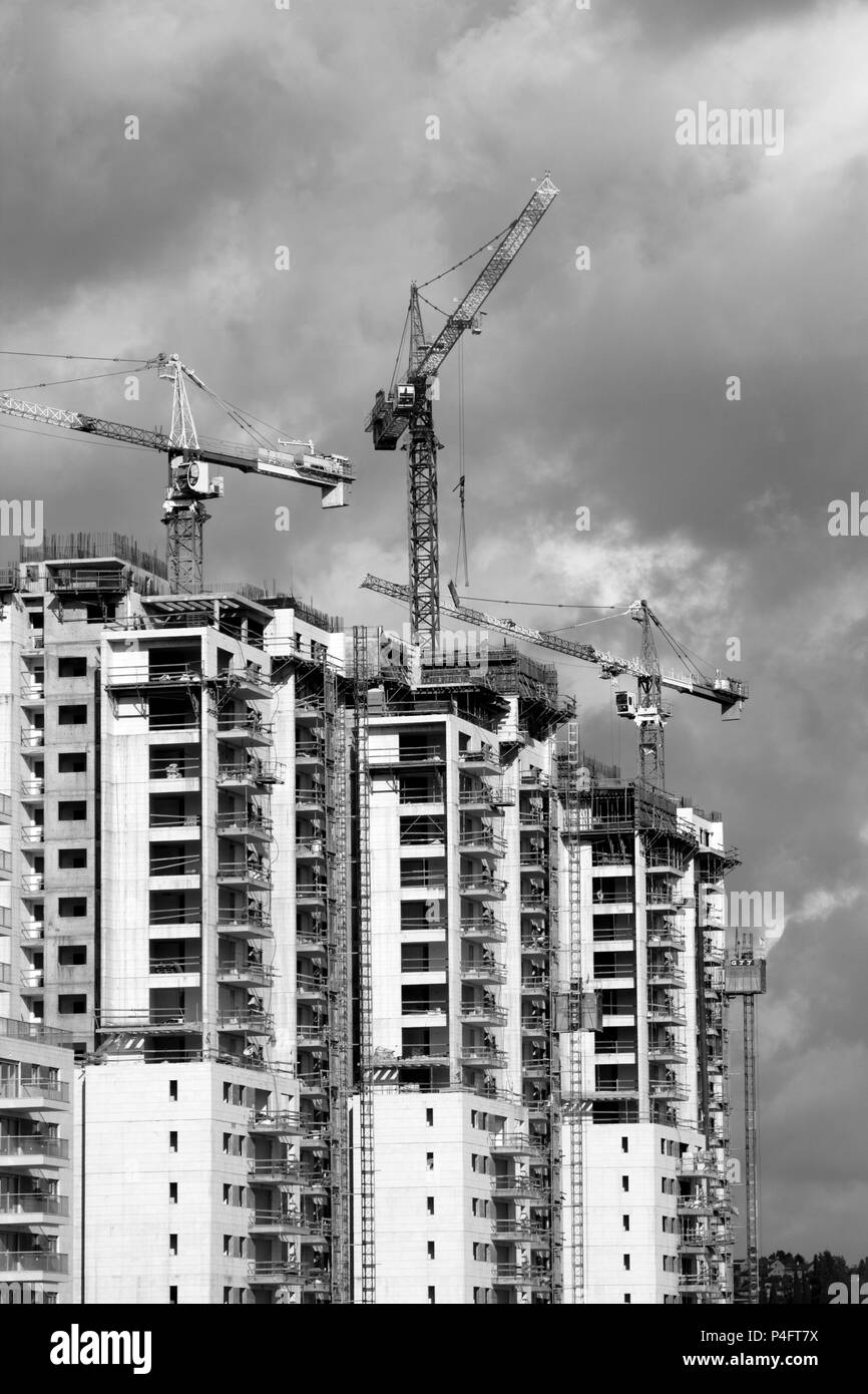 Construction work of high-rise residential buildings.Active construction of the housing complex, with the working cranes . - Stock Image