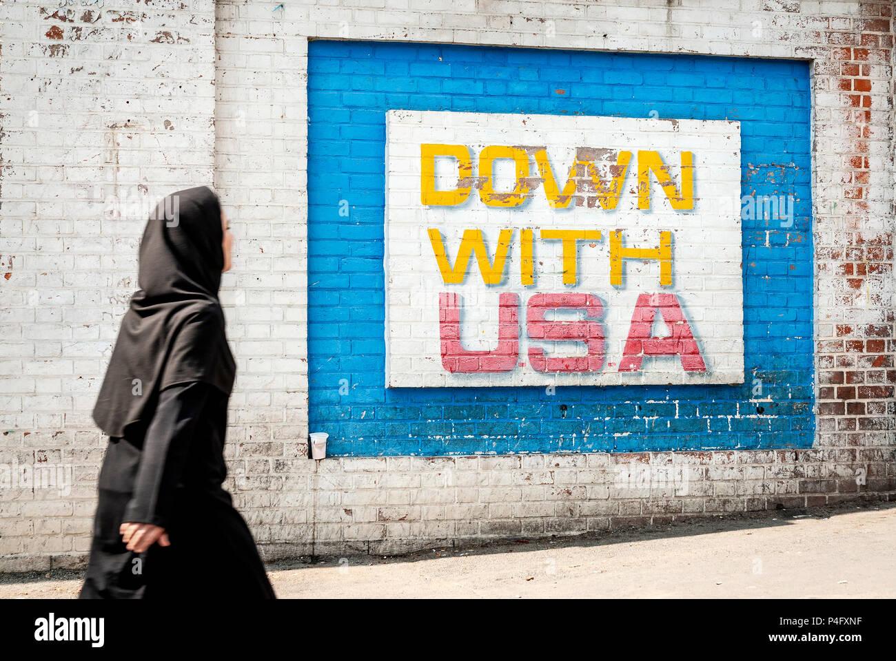 veiled muslim woman walking by anti american and israel propaganda mural on tehran street iran outside former US embassy - Stock Image