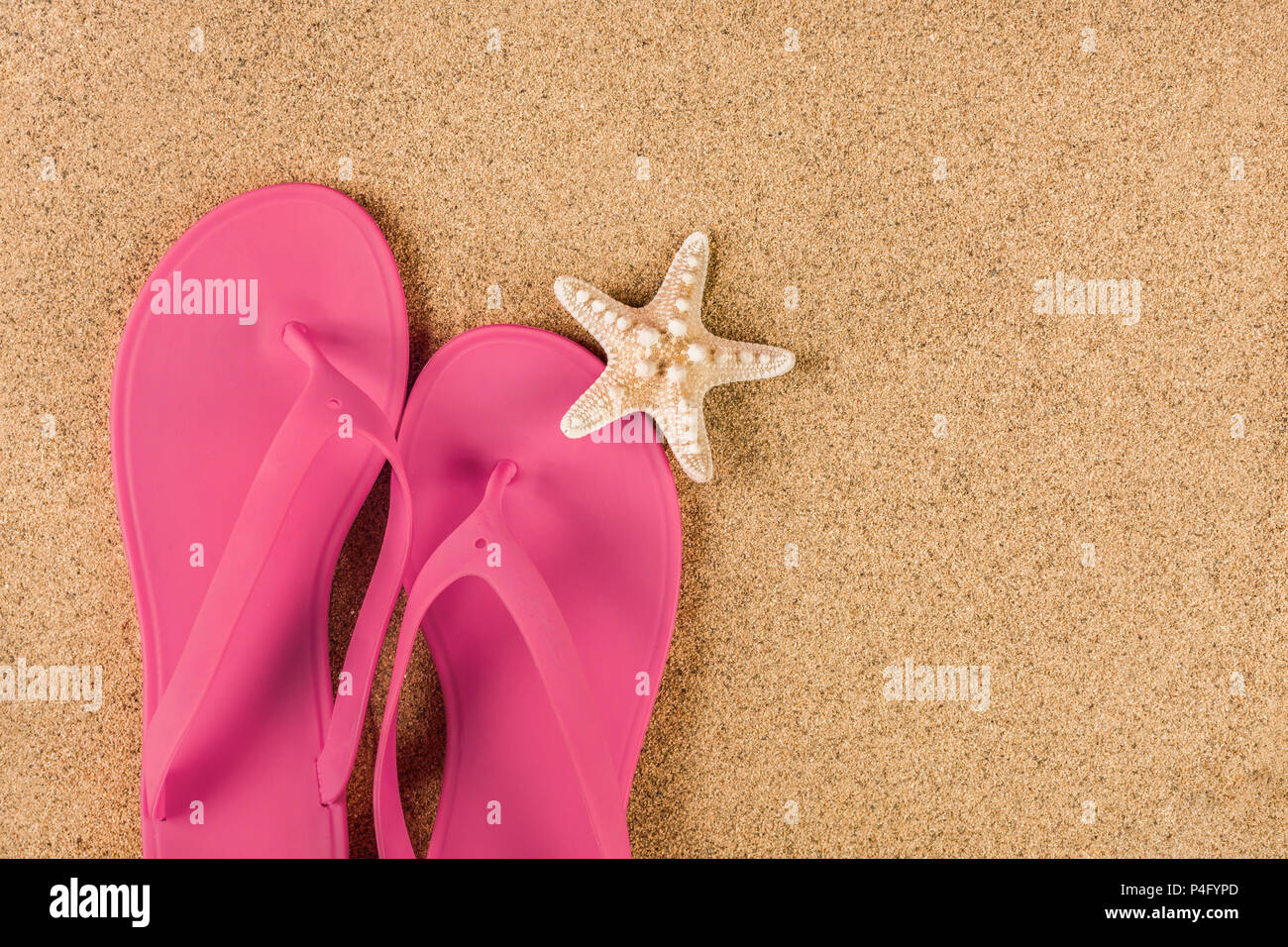 Pink sandal flip flop on sand beach and starfish. Summer vacations copy space and concept. Top view, close up - Stock Image