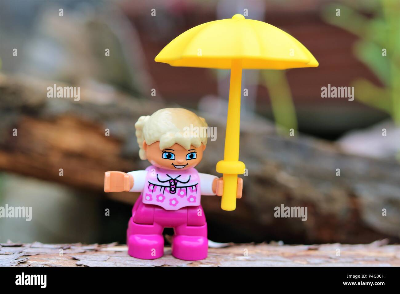 Duplo girl character holding a yellow umbrella against a blurred background - News Concept - Stock Image