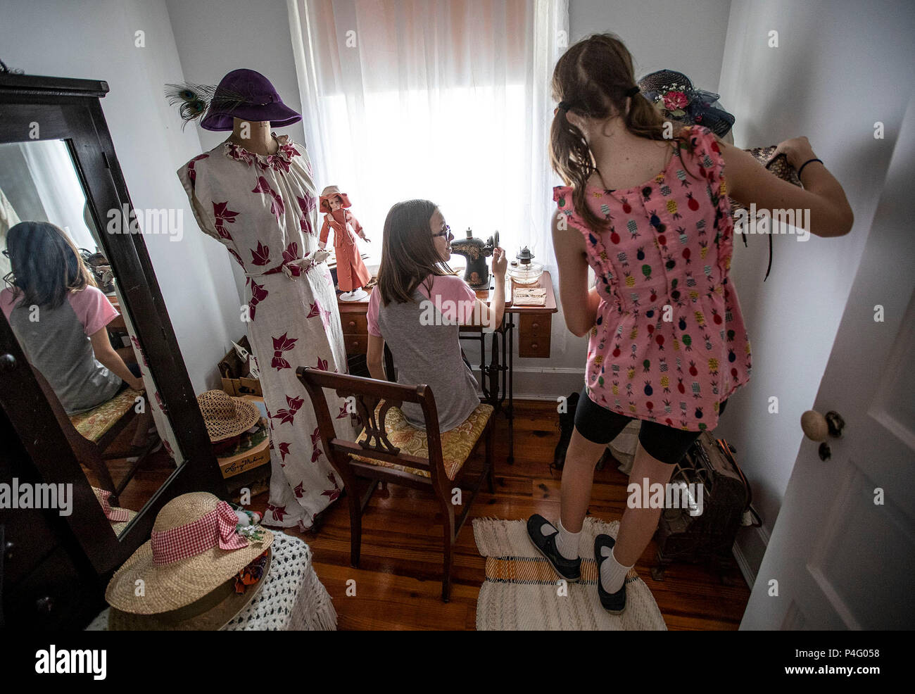 West Palm Beach, Florida, USA. 21st June, 2018. Coral Hodges, 12, Lake Worth and Isabella Ward, 11, Lake Clarke Shores explore the sewing room at the Riddle House in Yesteryear Village at the South Florida Fairgrounds in West Palm Beach, Florida on June 21, 2018. The house was built in West Palm Beach, Florida in 1905 by some of Henry Flagler's hotel construction workers. It was moved to Yesteryear Village in 1995. Credit: Allen Eyestone/The Palm Beach Post/ZUMA Wire/Alamy Live News - Stock Image