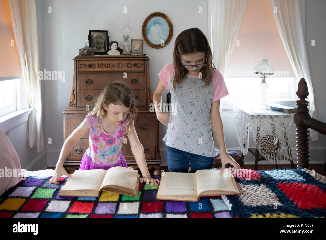 West Palm Beach, Florida, USA. 21st June, 2018. Summer Hodges, 6, and her sister Coral Hodges, 12, Lake Worth, look at old books at the Riddle House in Yesteryear Village at the South Florida Fairgrounds in West Palm Beach, Florida on June 21, 2018. The house was built in West Palm Beach, Florida in 1905 by some of Henry Flagler's hotel construction workers. It was moved to Yesteryear Village in 1995. Credit: Allen Eyestone/The Palm Beach Post/ZUMA Wire/Alamy Live News - Stock Image