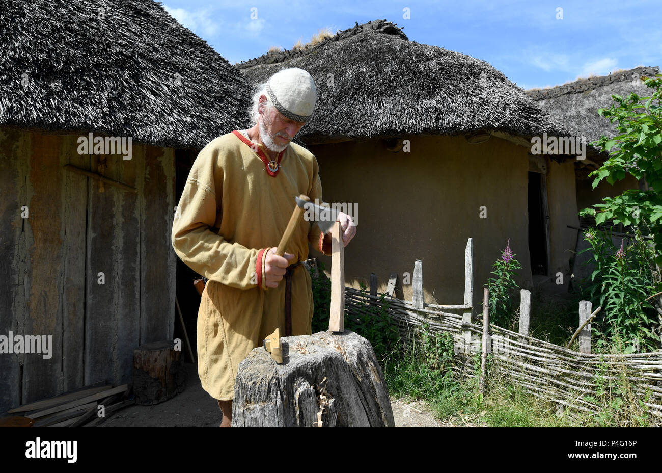 Danewerk, Germany. 19th June, 2018. A worker working in authentic Viking clothing on the site of the Viking houses in Hedeby. The UNESCO world heritage committee will decide on the admission of new monuments to its list at a session between the 24 June and 3 July. The Viking sites Hedeby and Danevirke are Germany's applicants. Credit: Carsten Rehder/dpa/Alamy Live News - Stock Image