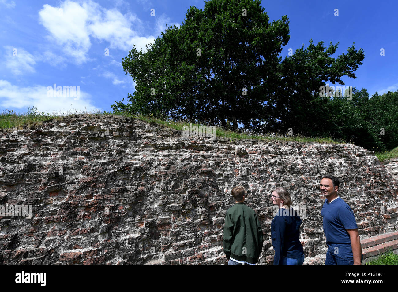 Danewerk, Germany. 20th June, 2018. Visitors standing on the Waldemar wall at the viking site Danevirke. It was originally made of mounds, walls, graves and a flood barrier in Schlei. The UNESCO world heritage committee will decide on the admission of new monuments to its list at a session between the 24 June and 3 July. The Viking sites Hedeby and Danevirke are Germany's applicants. Credit: Carsten Rehder/dpa/Alamy Live News - Stock Image