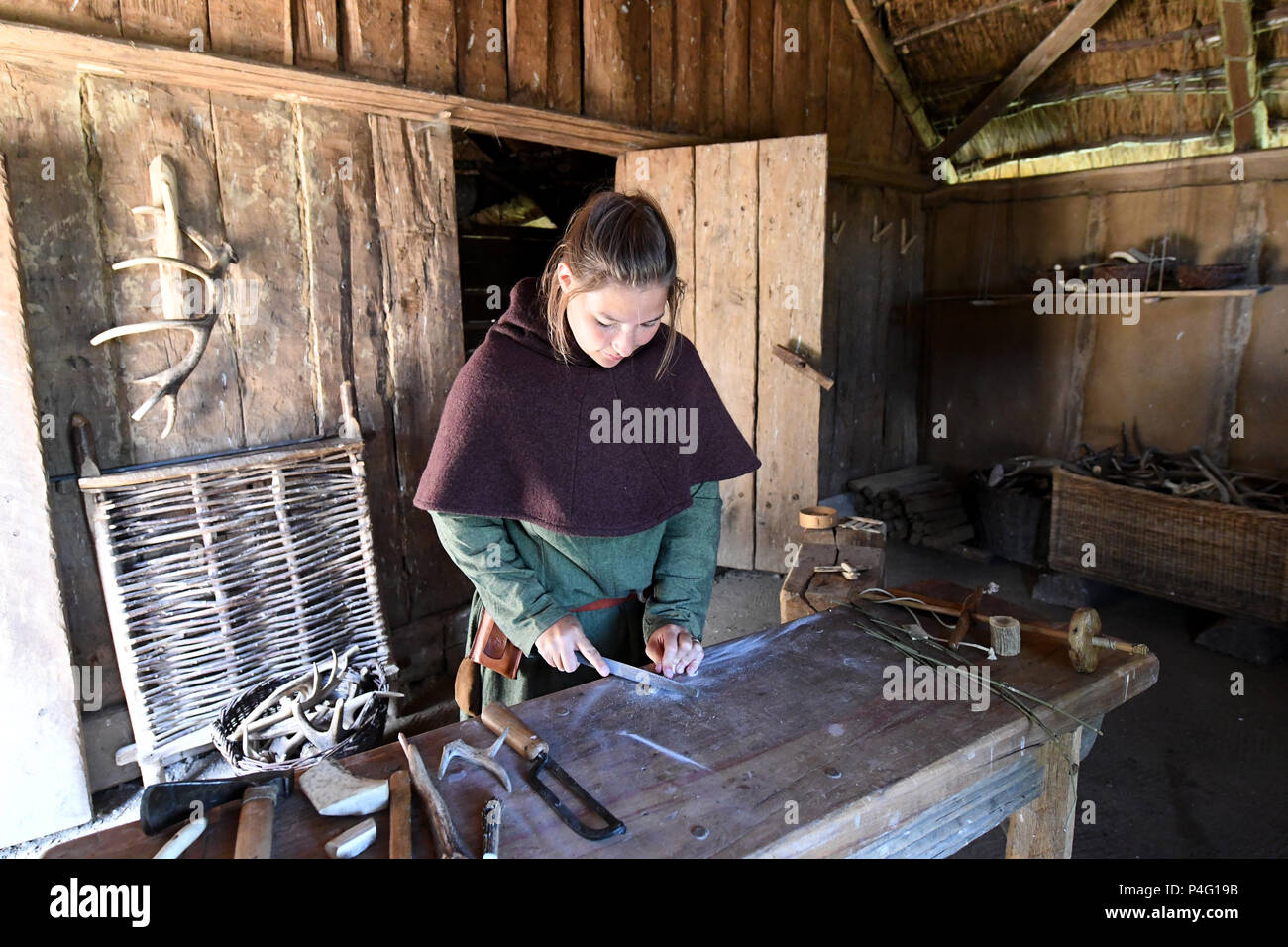 Danewerk, Germany. 19th June, 2018. Intern Caro working on a piece of jewellery in authentic Viking clothing on the site of the Viking houses in Hedeby. The UNESCO world heritage committee will decide on the admission of new monuments to its list at a session between the 24 June and 3 July. The Viking sites Hedeby and Danevirke are Germany's applicants. Credit: Carsten Rehder/dpa/Alamy Live News - Stock Image