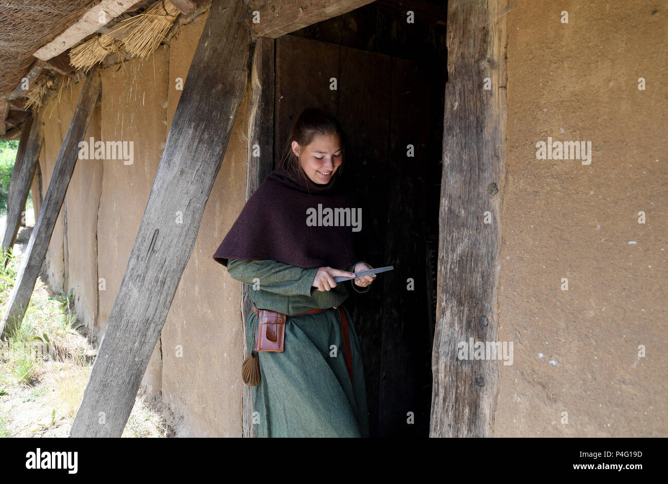 Danewerk, Germany. 19th June, 2018. Intern Caro working in authentic Viking clothing on the site of the Viking houses in Hedeby. The UNESCO world heritage committee will decide on the admission of new monuments to its list at a session between the 24 June and 3 July. The Viking sites Hedeby and Danevirke are Germany's applicants. Credit: Carsten Rehder/dpa/Alamy Live News - Stock Image