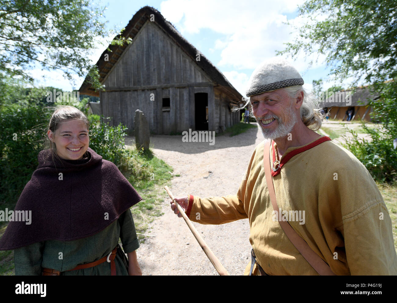 Danewerk, Germany. 19th June, 2018. Workers in authentic Viking clothing standing on the site of the Viking houses in Hedeby. The UNESCO world heritage committee will decide on the admission of new monuments to its list at a session between the 24 June and 3 July. The Viking sites Hedeby and Danevirke are Germany's applicants. Credit: Carsten Rehder/dpa/Alamy Live News - Stock Image