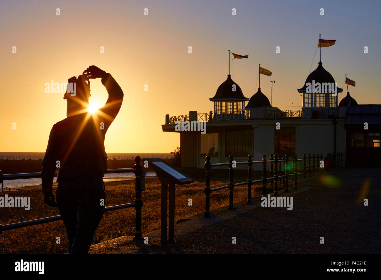 Herne Bay, Kent, UK. 22nd June 2018: UK Weather. A Glorious and clear sunrise at Herne Bay. The Stephen Melton statue of Amy Johnson who went missing off Herne Bay in 1941, stands facing the sunrise and the bandstand. High temperatures and fine weather are predicted to last into next week. Credit: Alan Payton/Alamy Live News - Stock Image