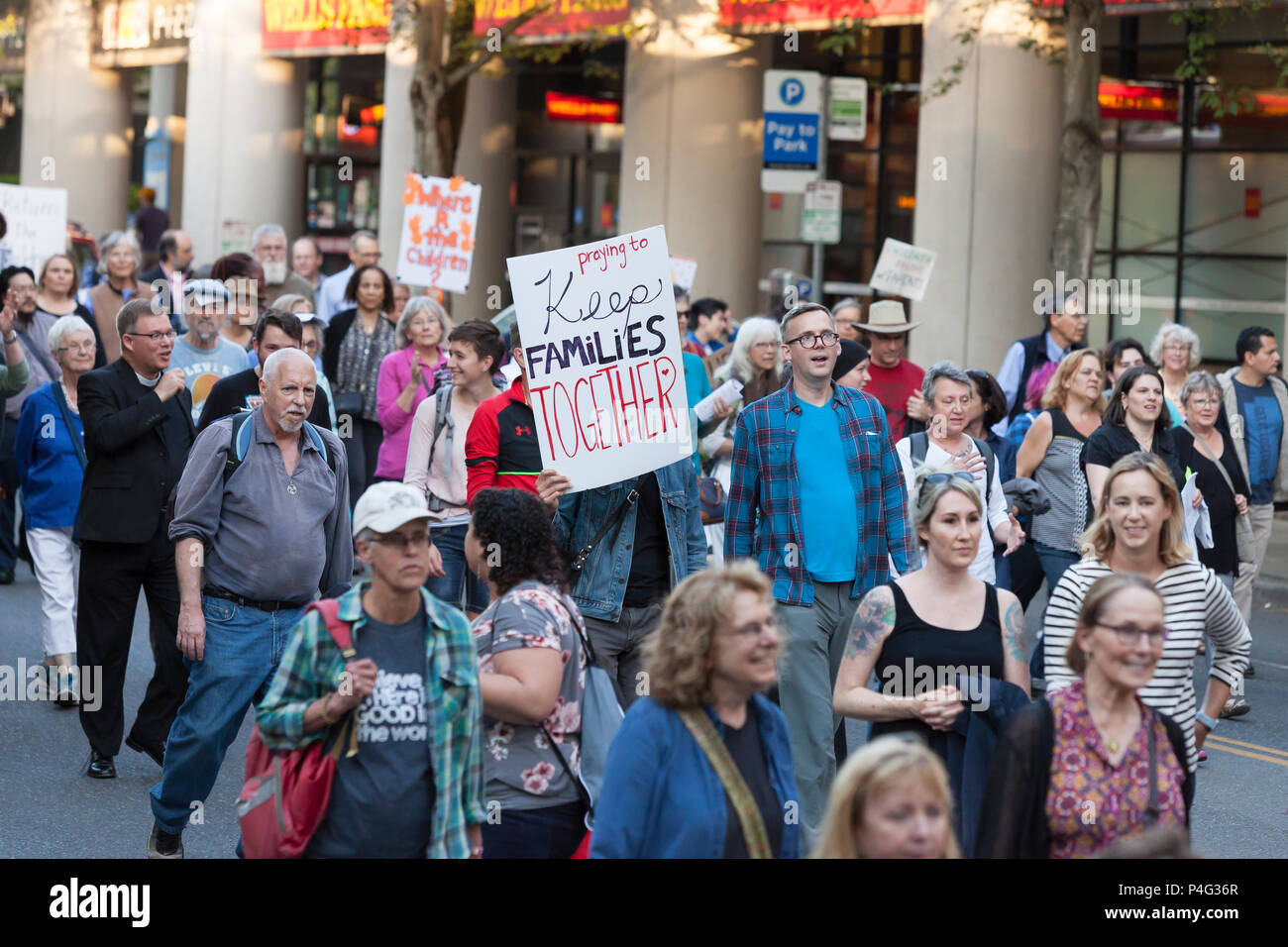 Seattle, USA. 21 June 2018. A contingent of clergy leads a procession along Broadway Avenue E. Hundreds of supporters gathered at St. Mark's Episcopal Cathedral in Capitol Hill for an interfaith prayer and vigil in support of migrants and asylum-seekers who come to the U.S. and to protest the inhumane separation of children from their parents. The two mile 'Prayer and Procession for Families at the Border' began at Saint Mark's Episcopal Cathedral in ended at St. James Roman Catholic Cathedral in First Hill. Credit: Paul Christian Gordon/Alamy Live News - Stock Image