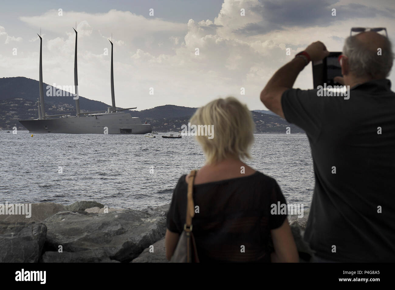 """Saint Tropez. France 21th, 2018. People look at the big """"Sailing A"""" in front of Saint Tropez Gulf. The  Sailing A is the biggest sailing yacht in the world, build in Germany with the most advanced technology. Lenght 142.81 meters; 12700 tons, designed by Phillippe Starck and Dolker & Voges. The owner of the ship is Andrei Melnichenko from Russia. Photo Alejandro Sala/Alamy Llive News Stock Photo"""