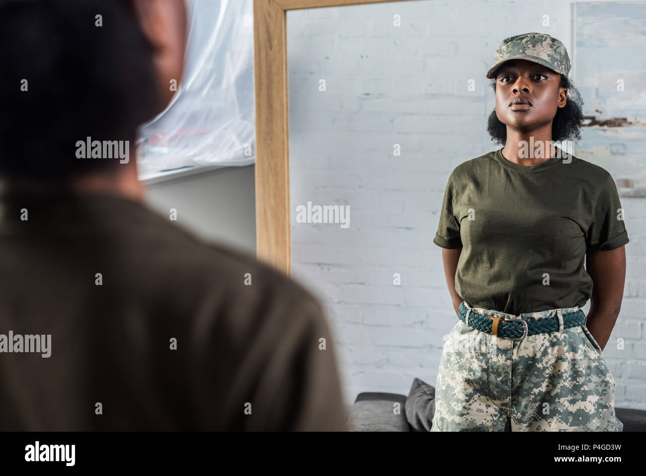 Confident african american woman in camouflage clothes posing by the mirror - Stock Image