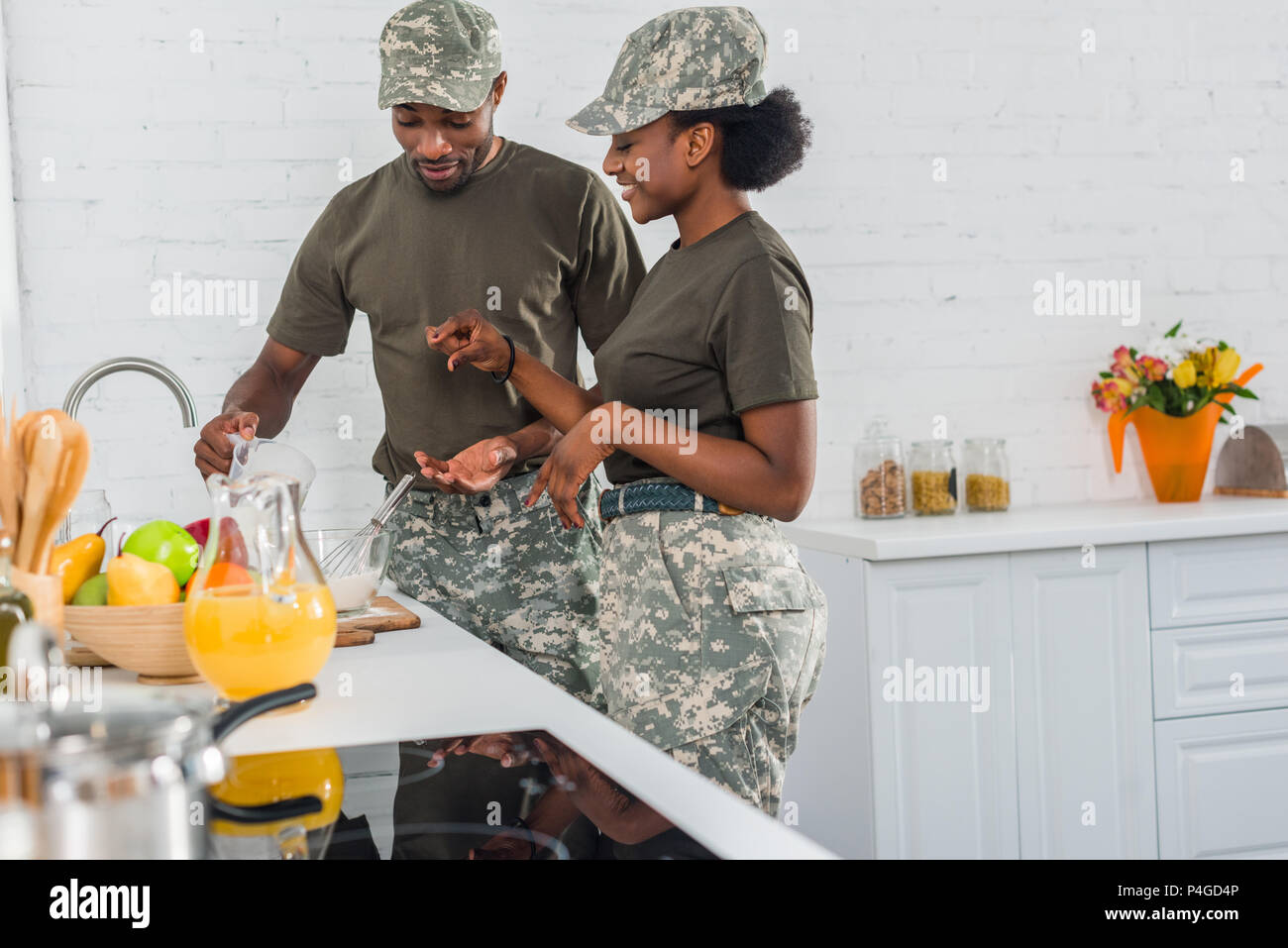 African american female soldier with man cooking together at home kitchen - Stock Image