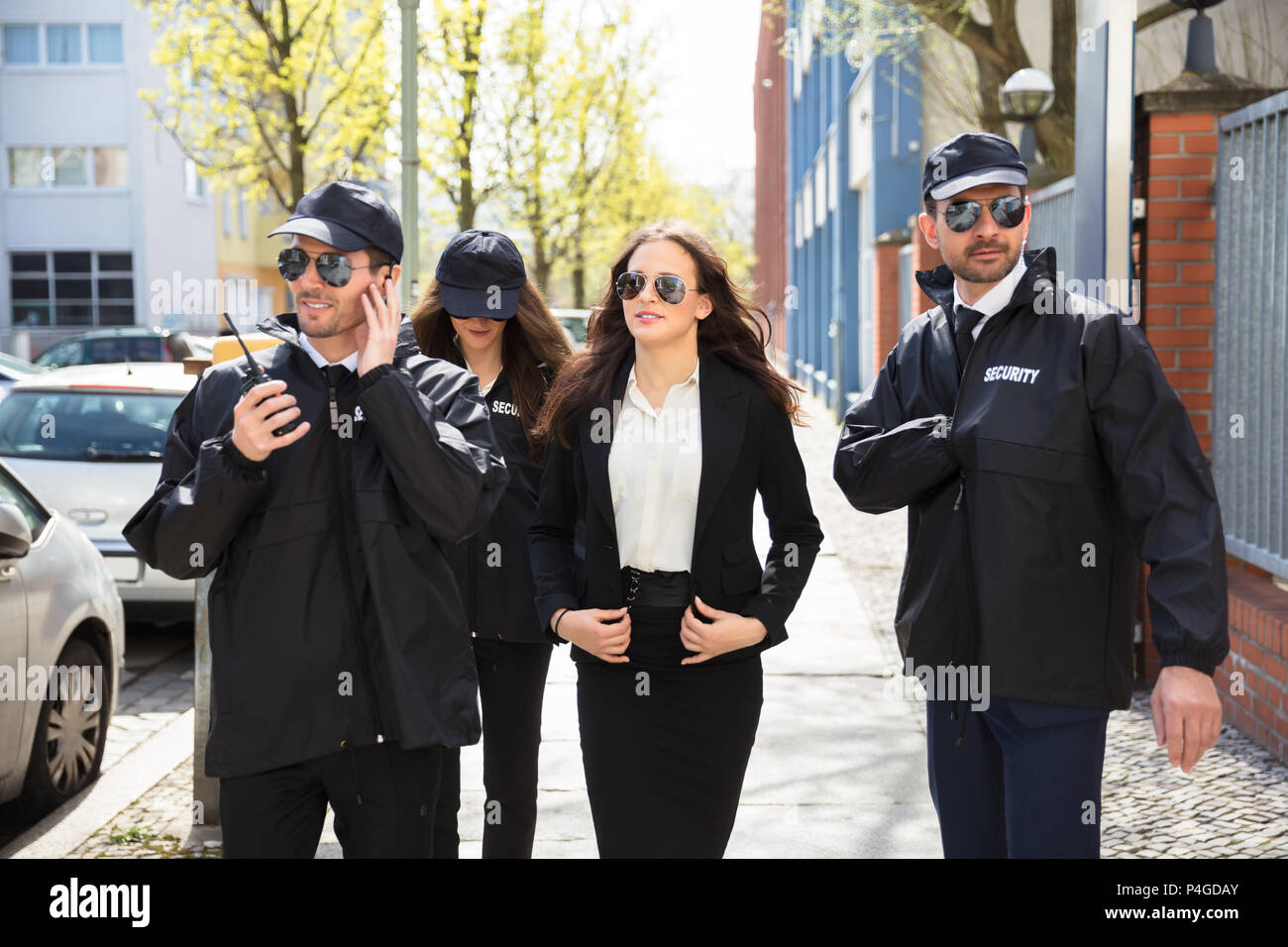 Portrait Of Young Female Celebrity With Bodyguards Walking On Sidewalk - Stock Image