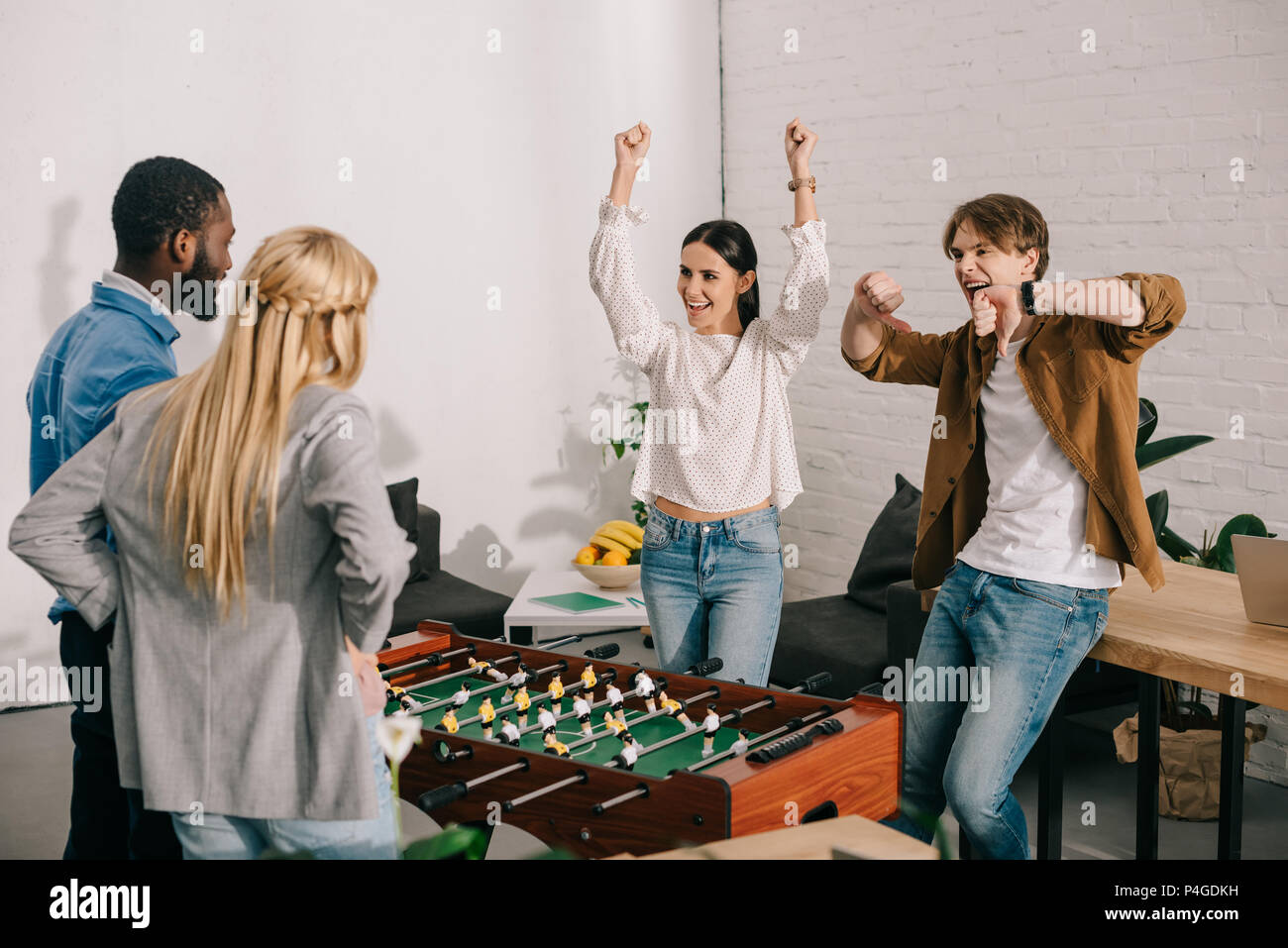 happy business partners celebrating victory in table football with arms up and thumbs down gestures in front of colleagues - Stock Image